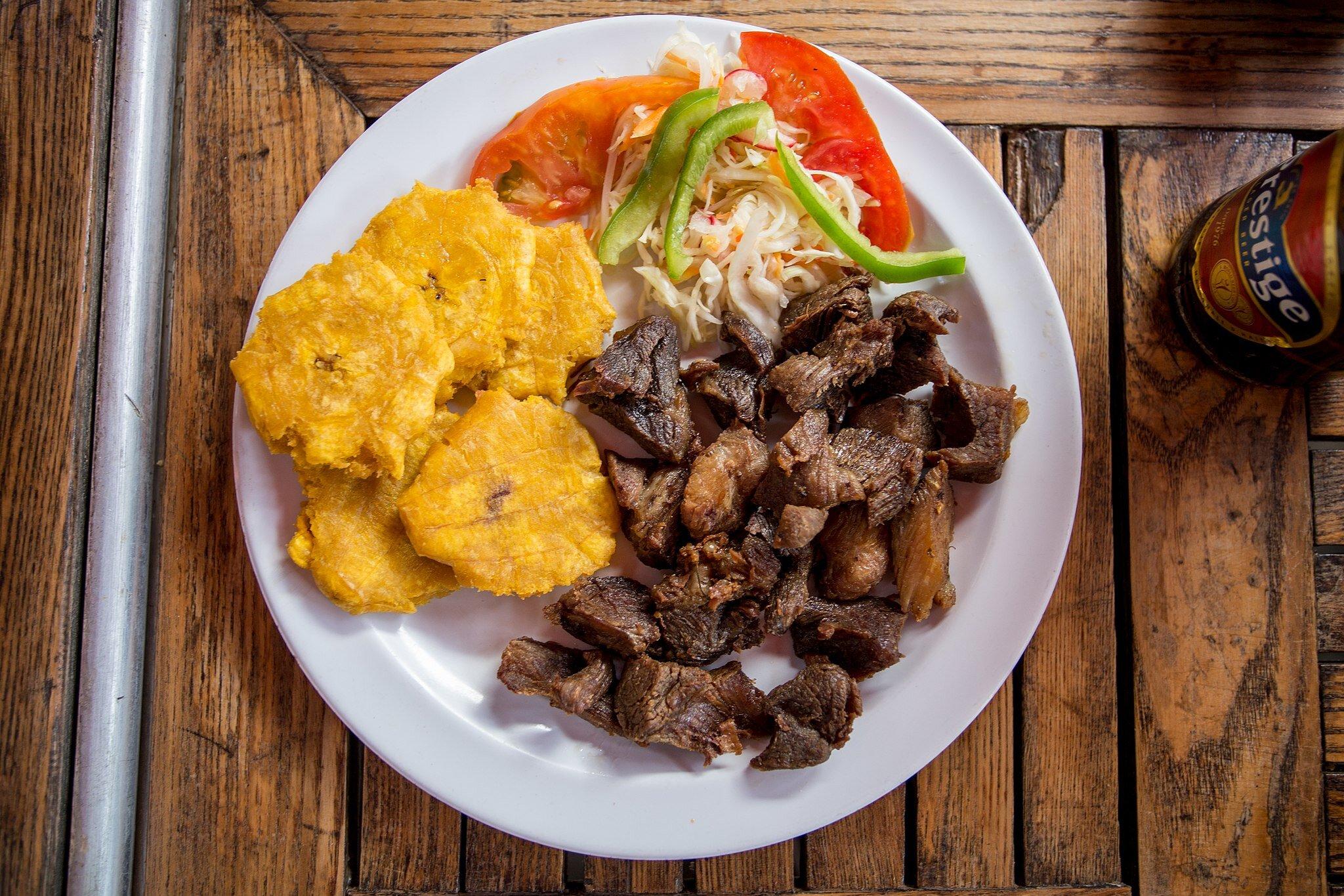 Griyo是海地的国菜。这里有车前草和啤酒。图片来源:Lëa-Kim Châteauneuf, CC BY-SA 4.0,通过维基共享。