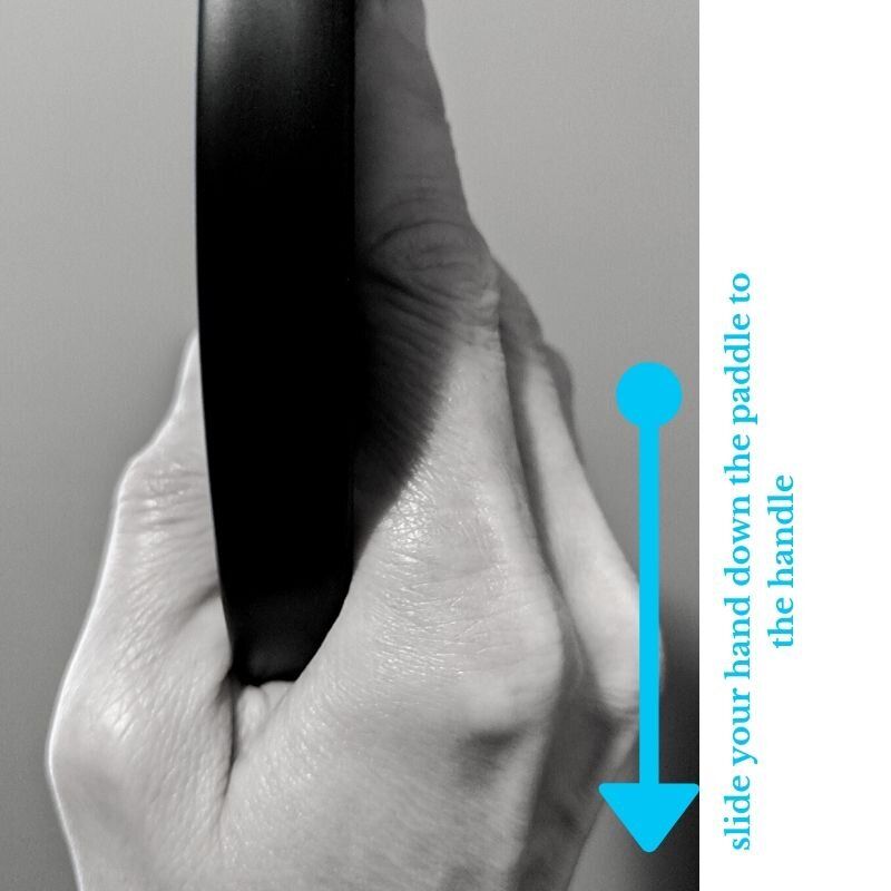 Slide hand directly down paddle to grip handle