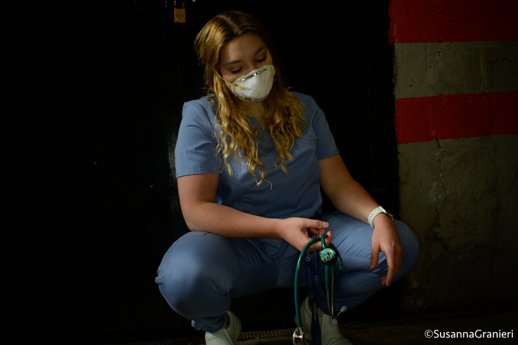 "Bruno kneels down holding her stethoscope. She has a personalized ID tag on it saying ""It's a beautiful day to save lives,"" from ABC's Grey's Anatomy."