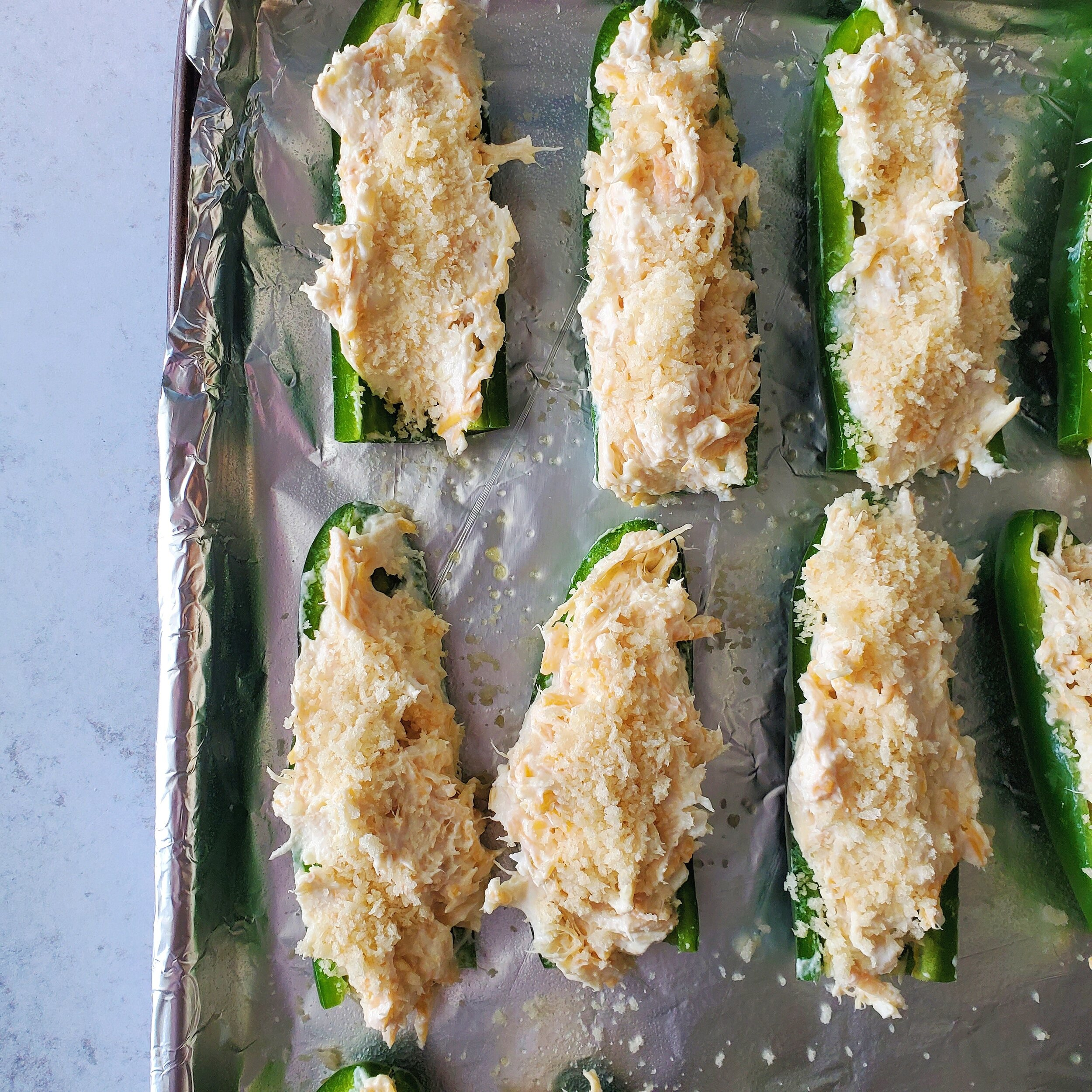 Line a cookie sheet with aluminum foil, then spray with non stick spray.With a small spoon add the filling to each jalapeno. Spread the filling so it is even.Next sprinkle the bread crumbs on top. Bake at 375 for 15 minutes. -