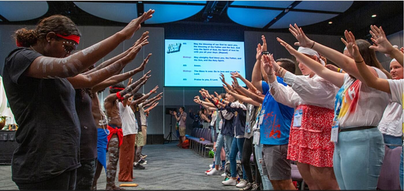 Indigenous and non-Indigenous young people pray over one another during the Missa Terra Sancti Spiritu, the Mass of the Land of the Holy Spirit, during Day 2 of the Australian Catholic Youth Festival in Perth. Image: Mary Brazell/Diocese of Parramat…