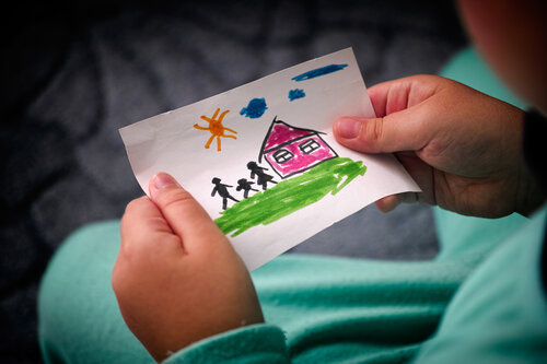 A child holds a drawing of their home, family and garden.