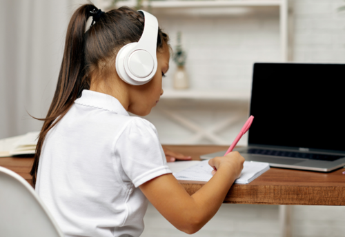 Student, wearing headphones, writes in notebook, sitting at desk in front of laptop