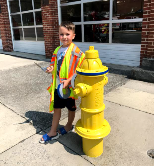 Image of a child standing next to a fire hydrant