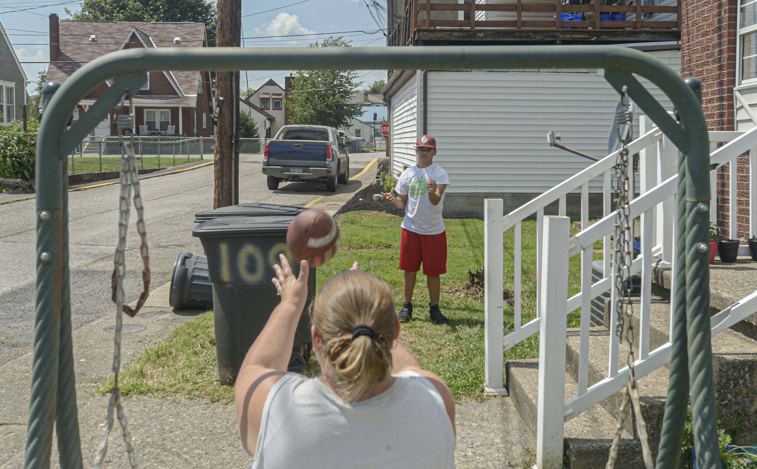 "Jessica Smith, foreground, tosses a football with her son, William Smith, outside the family home in Belle on July 9, 2020. Smith said her son ""seems like he's never full"" this summer as the family struggles to access food during the COVID-19 pandemic. Photo by F. Brian Ferguson"