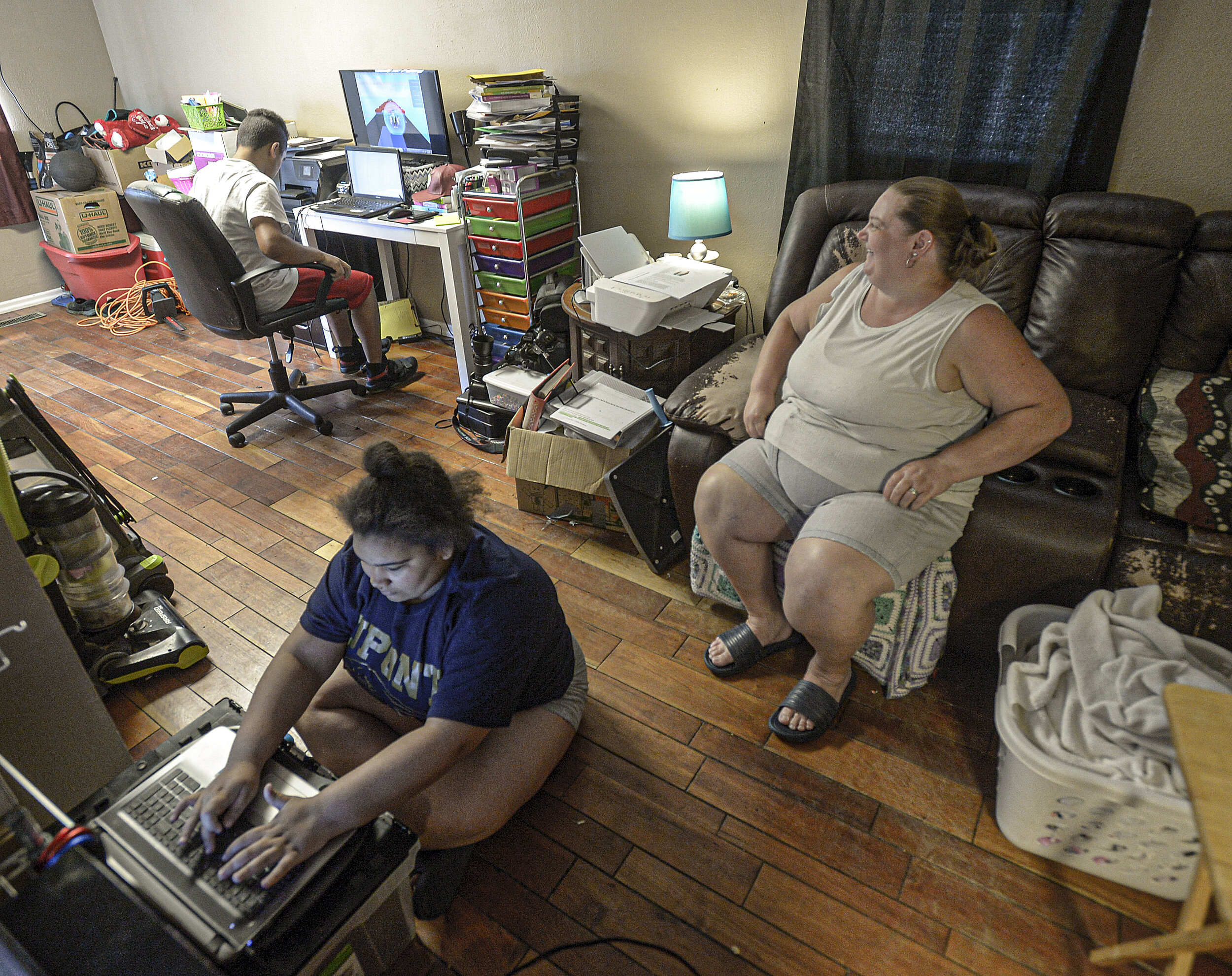 Angelica Smith, 14, left, plays a video game as her brother William Smith, 13, background, works on the family computer. Their mother, Jessica Smith, looks on in the family home on July 9, 2020 in Belle. The family is not able to get to their designated summer feeding site because they do not own a vehicle. Photo by F. Brian Ferguson