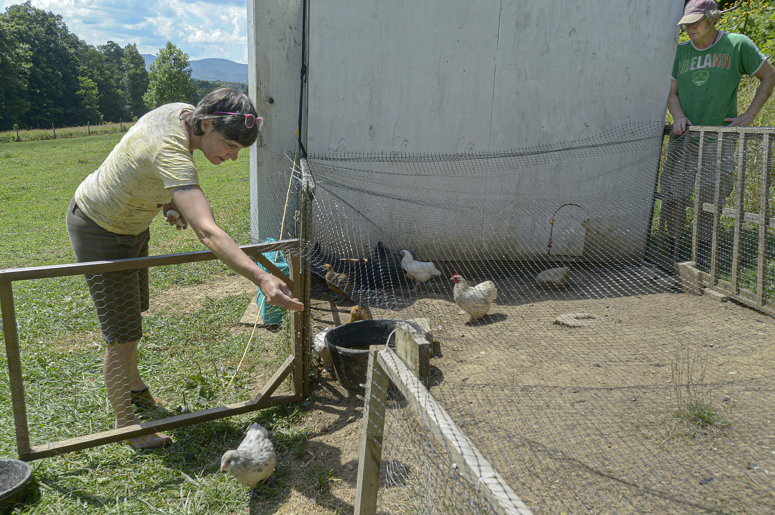 Jennifer Boyle-Hempel, left, and her husband, Kevin Boyle, feed chickens on their family farm on July 13, 2020, in Randolph County. Photo by F. Brian Ferguson