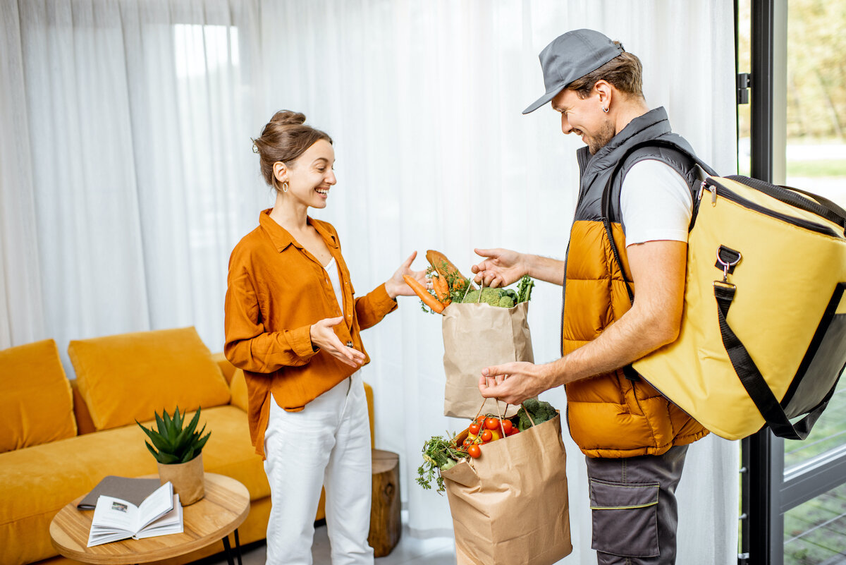 Happy woman receiving order from delivery.jpg