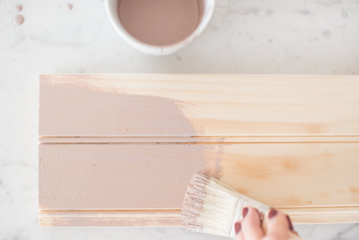 Arabesque Milk Paint by Miss Mustard Seed being brushed onto a raw wood board