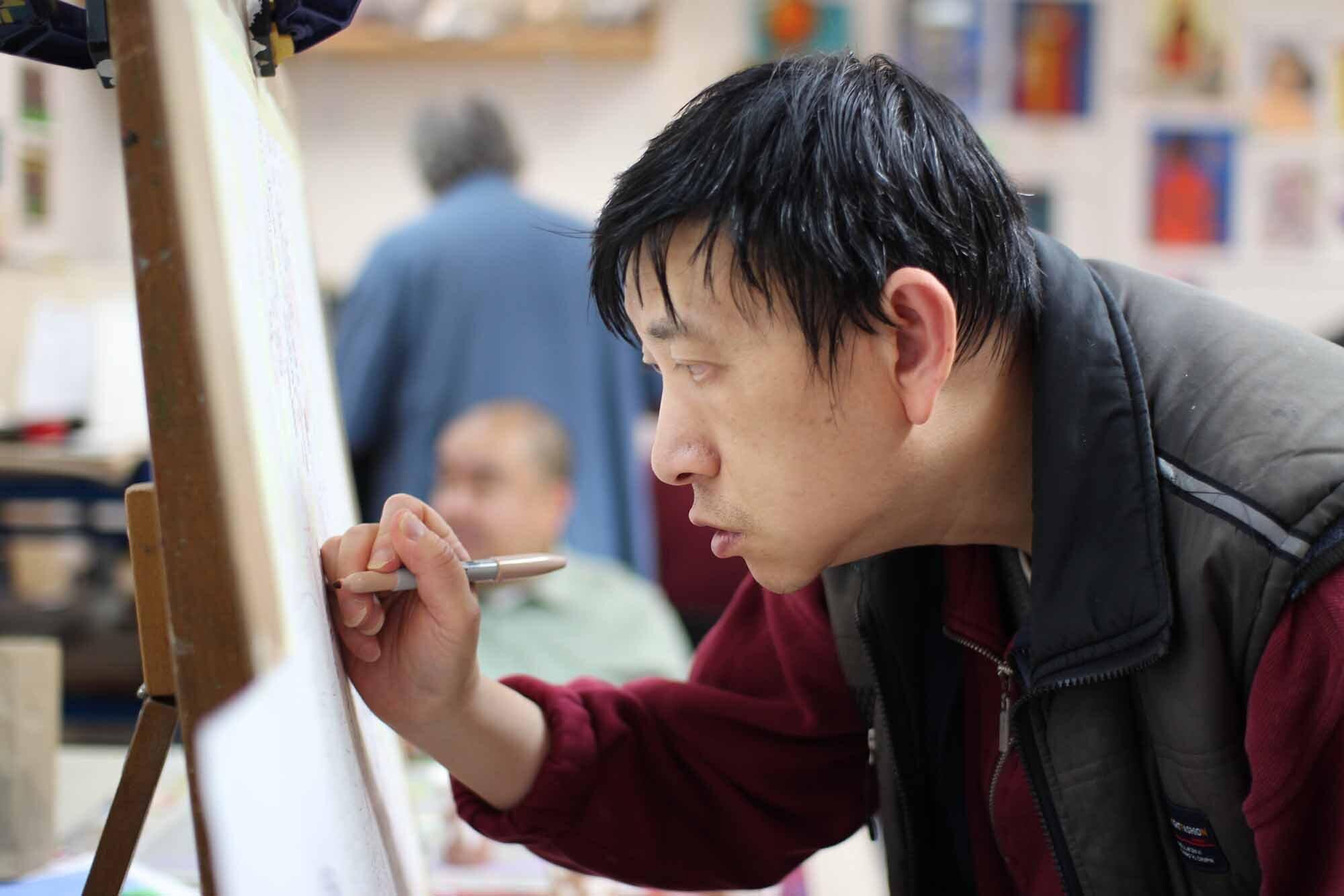 CE artist Hung Kei Shiu, a man of Asian descent, drawing in the studio.jpg