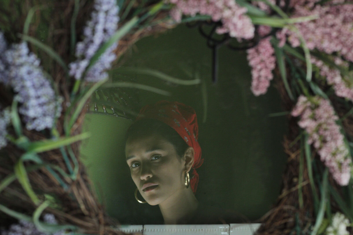 An art photo with the reflection of a woman's face looking inside a floral wreath.