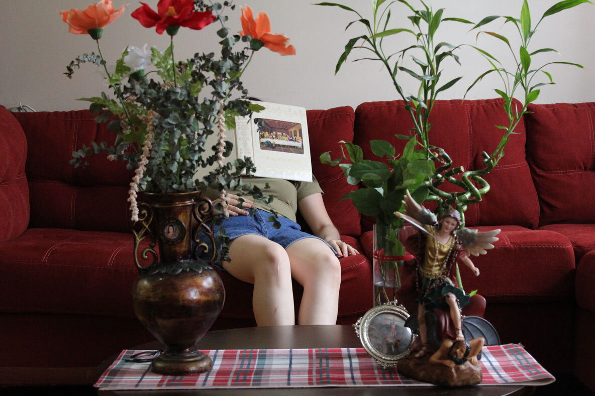 An art photo of a red couch with a young person leaning back on it with a book over their face. In the foreground is a large, tall bouqet and an angel statue on the coffee table.