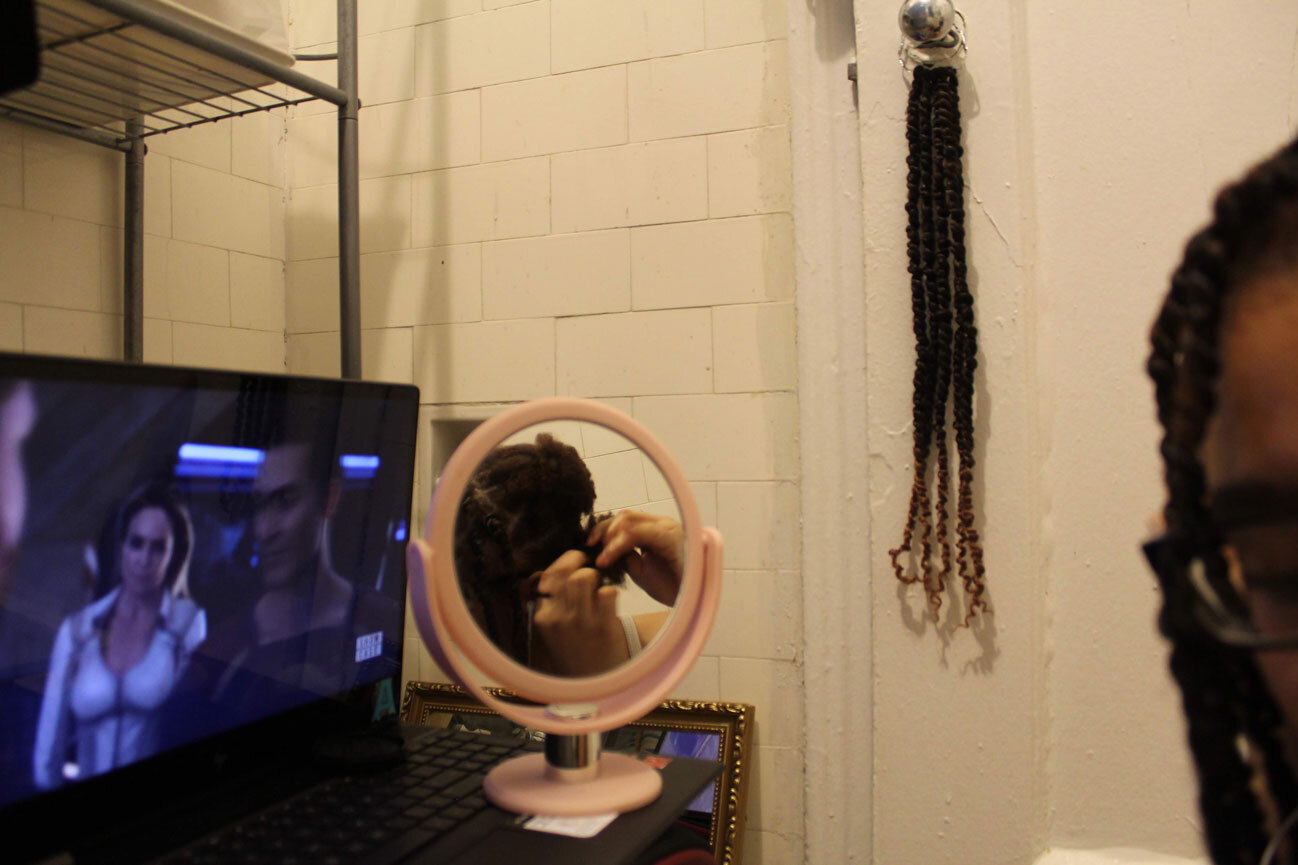 A photo of a small circular mirror on a counter next to a laptop showing a TV show. Reflected in the mirror you can see the hands of a teen girl braiding her hair.