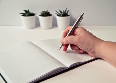person-holding-silver-retractable-pen-in-white-ruled-book-796603.jpg