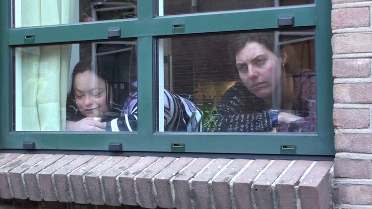 Two people look out of a window. On looks sad and one smiles.