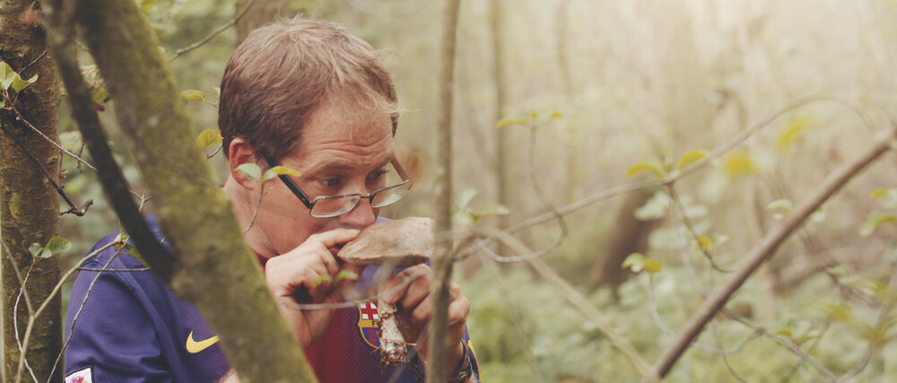 Man wears glasses smells a large mushroom in a green forest.