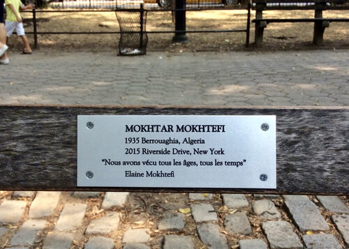 """Nous avons vécu tous les âges, tous les temps  (""""We've lived every age, every time"""") is a line from a poem written by the author to his wife. This line is emblazoned on the memorial bench in Riverside Park, New York City dedicated to Mokhtar Mokhtefi after his death in 2015 (photo Suzanne Ruta)."""