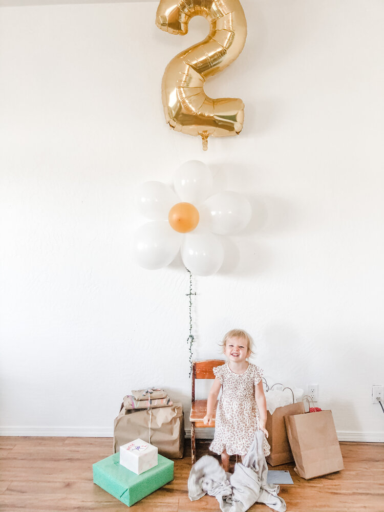 """I bought a bunch of balloons in white, gold and yellow to do that balloon arch in the kitchen, but the wall in the living room was pretty bare so my mom who was in town visiting had the idea to make a daisy out of the balloons and the greenery from those dollar spot balloons as the stem. It worked out perfectly as a little photo-op area where she opened her presents.  Overall I had  so  much fun planning and decorating for this party. We only had two families over who happen to be both of our neighbors so it was super intimate and precious and I loved that.  If you're anything like me when you are looking for birthday party ideas, you want the cut and dry post with links to everything. """"I love that, I want that, where is the link for that?"""" So I figured I would make it easy for you guys and link as much as I can in this post. Some of the links may be affiliate links and earn me some income that helps keep this blog afloat. Thanks for your support, Darlings <3     Decor:    Vintage Mustard Floral Fabric    White and Gray Striped Fabric    Cream and Charcoal Striped Fabric    Balloon Arch    White Balloons with Greenery    '2' Balloon    'Tea for Two' Balloon Banner    Or Separate Gold Balloons    Daisy Plates    Gold Forks    White Napkins    Vintage Cake Stand    Craft Daisies for Confetti    Vintage Floral Dress"""