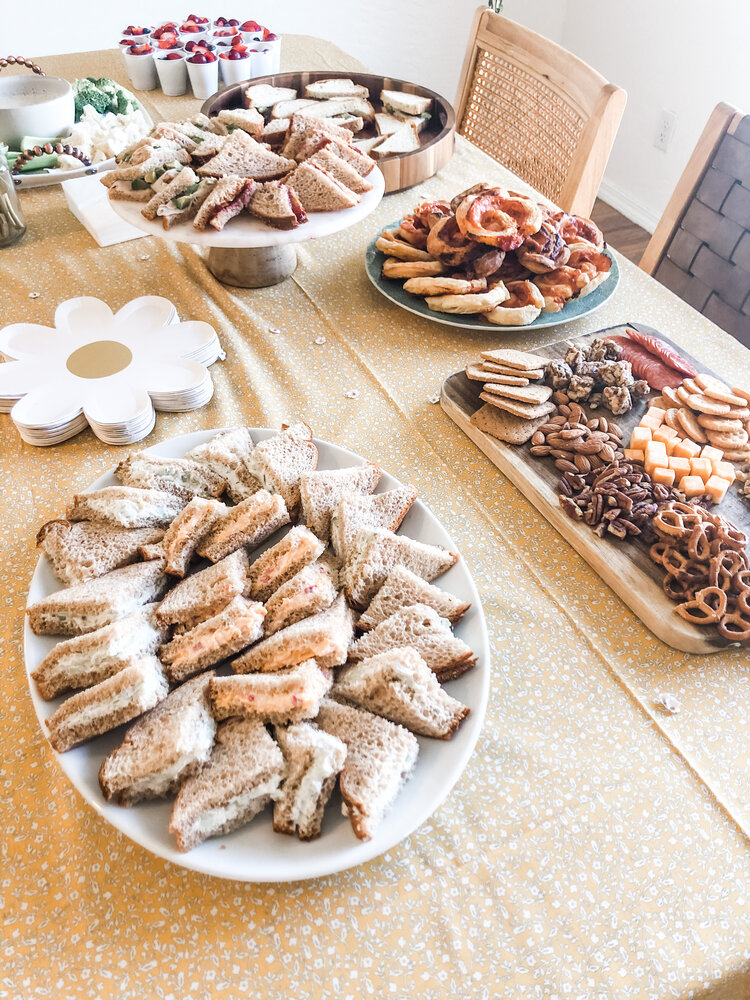 Now for the food table. Admittedly my favorite part. I  had  to make a bunch of tea sandwiches for the tea party, right? I went with the classic cucumber sandwich and pimento sandwich on regular bread, and because half of our guests are dairy and gluten free I did peanut butter & jelly and a turkey & avocado on gluten free bread. One of my favorite party foods is the puff pastry pizza rolls- so YUM! I also did a simple charcuterie board with cheese, meat, gluten free crackers, gluten free pretzels, nuts and fruit/nut clusters, which I felt was perfect for a kid party. A veggie tray with homemade ranch and little fruit cups were also great for snacking and little hands.