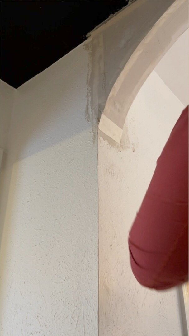 Use a small piece of tape the width of the arch to make a seamless transition into the wall.