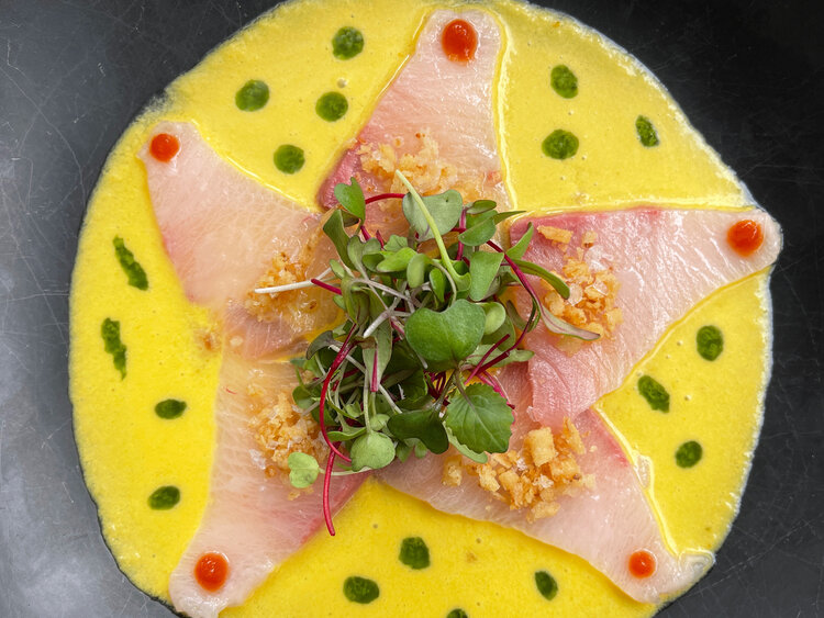 """Himachi tiradito was the first appetizer served and this dish was as flavorful as it was colorful. The Hamachi was served with a melon, yellow pepper and yuzu sauce that gave it a bright yellow """"leche de tigre-ish"""" color and complimented well with t…"""