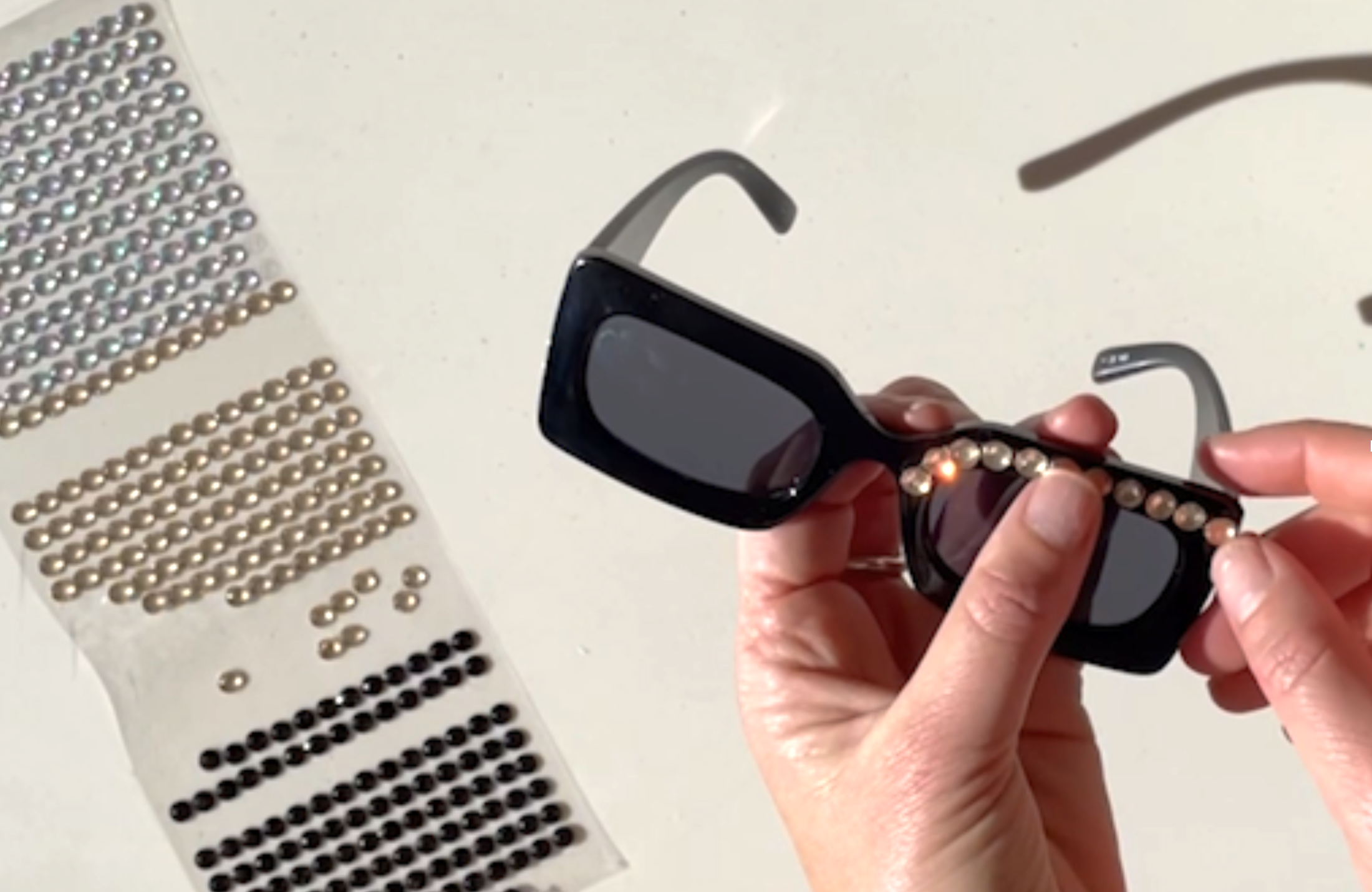 Take a whole row of rhinestones from your pack. Starting at the bridge of the nose, stick the rhinestones across the top of the sunglasses. Tear off any stones that don't fit straight across the top.