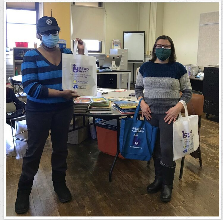 Mary Wilson and Deicy Perez from Beyond Literacy distributing bags of books and materials to families.