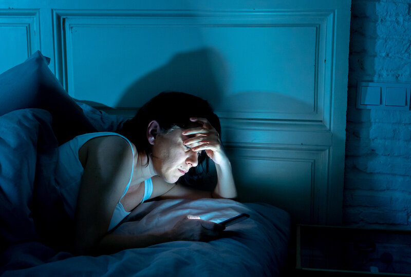 Woman on phone in bed.jpeg