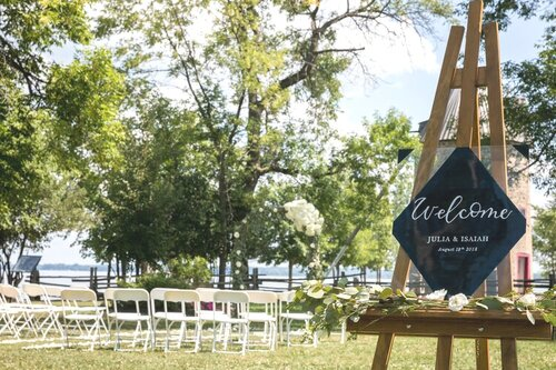 outdoor wedding ceremony with acrylic sign on wooden easel